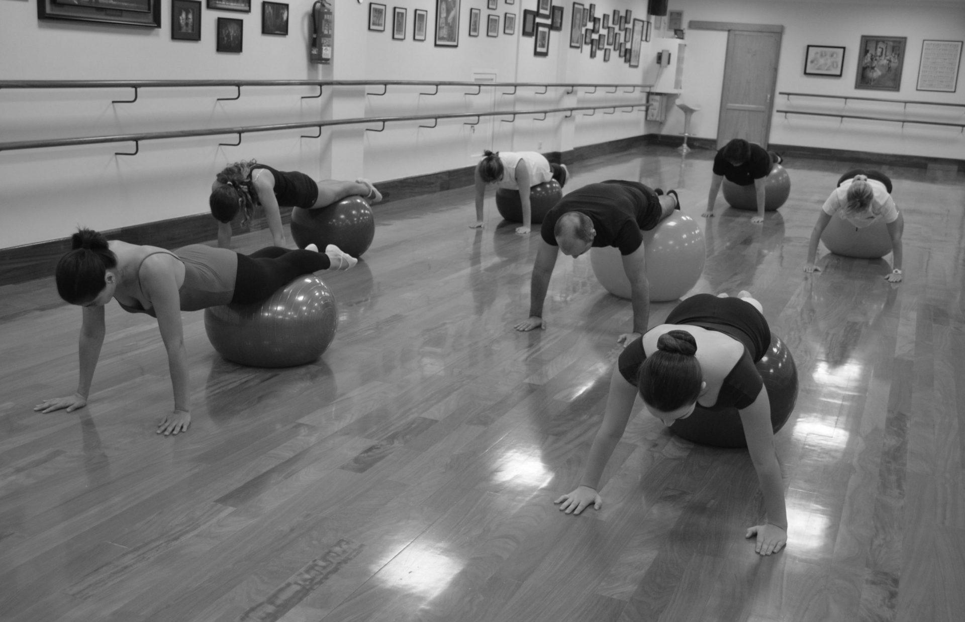 Foto en el Centro de Danza Sandra Santa Cruz donde un grupo de alumnos hacen un equilibrio en plancha con las manos en el suelo y los pies sobre una pelota grande durante una clase de Stretching con fit-ball y bandas elásticas para tener mejor forma física.