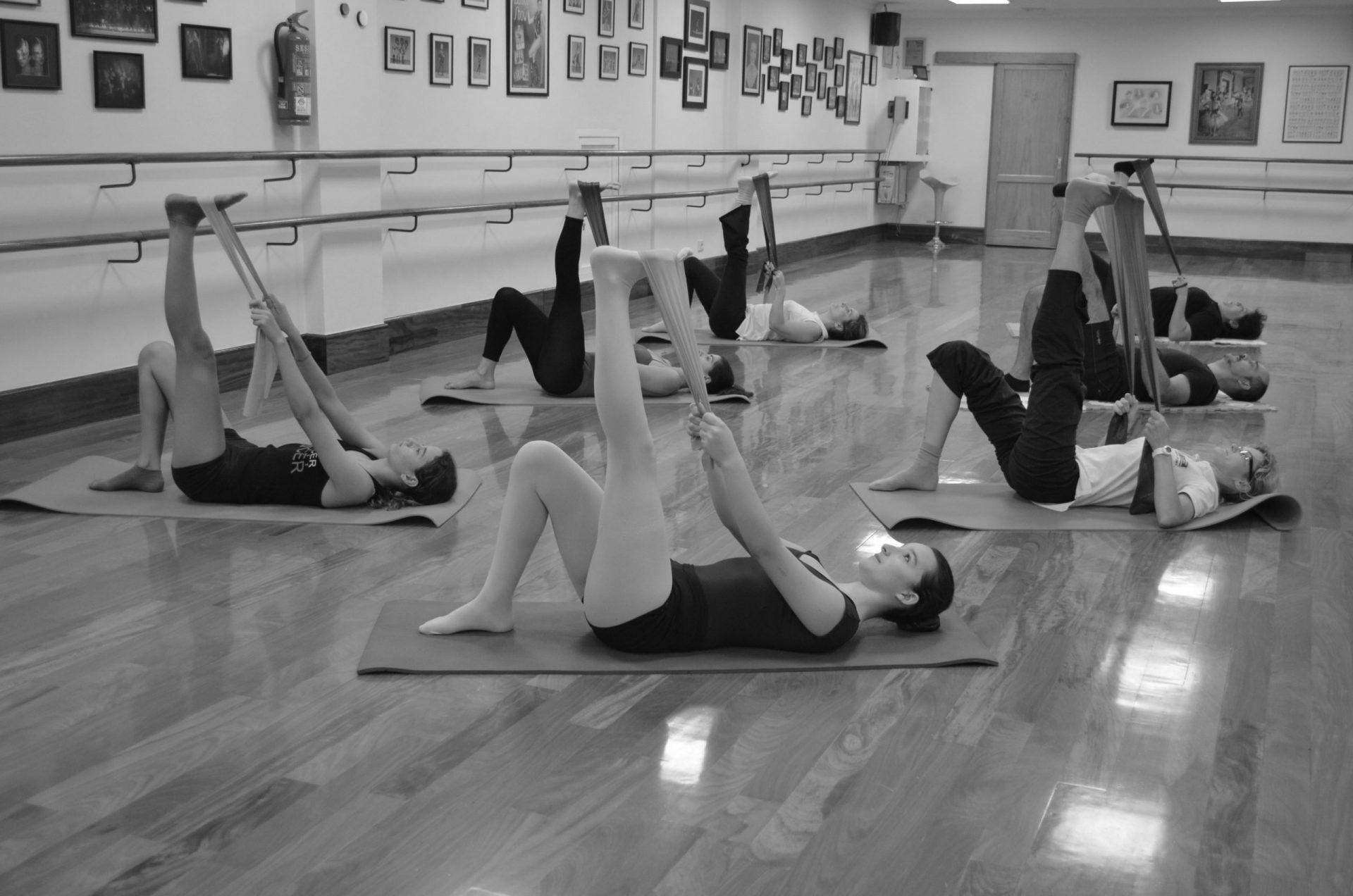 Foto en el Centro de Danza Sandra Santa Cruz donde un grupo de alumnos acostados en una colchoneta tienen un pie elevado que sujetan con una banda de paraband durante una clase de Stretching con fit-ball y bandas elásticas para tener mejor forma física.