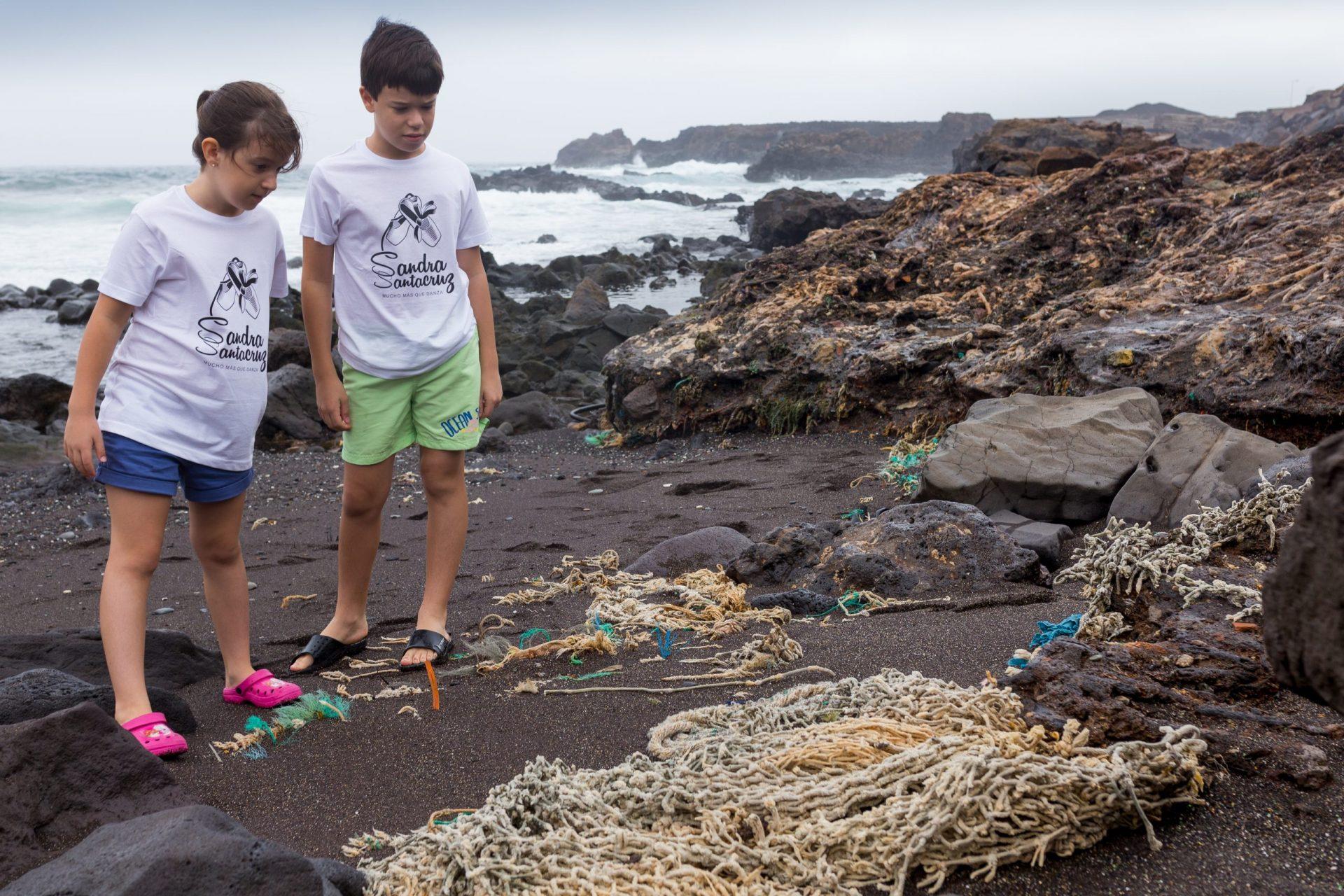 """Foto de un niño y una niña en una playa en Gran Canaria mirando entre asombrados y entristecidos como redes y desechos tirados por el hombre se han ido integrando con el paso del tiempo y se mimetizan con el entorno, convirtiéndose ya en parte de las rocas. Es desolador que hayamos formando un triste entorno que con responsabilidad podemos evitar. Para celebrar el Día Internacional del Libro Infantil y Juvenil de 2021 Sandra Santa Cruz, autora de """"Si los peces hablaran...""""  hace una campaña de concienciación sobre la contaminación marina con alumnado de su Centro de Danza  Sandra Santa Cruz (del que es directora y profesora) que lleva puesta la camiseta del Centro, ya que llevan desde el 2016 trabajando en este proyecto que nace gracias a la filosofía del Centro: """"Muchomasquedanza"""" que trabaja valores a través de la danza. Con esta fotografía de Ethel Bartrán buscamos que: ¡No te quedes de Aletas Cruzadas!"""